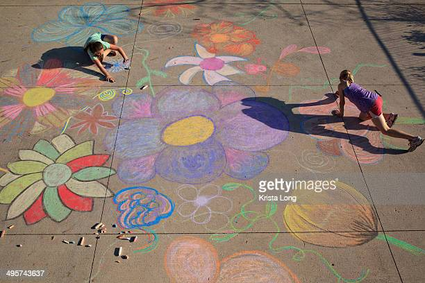 Two children drawing with chalk on concete.