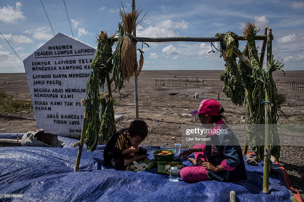 Two children eat after they pray together at mudflow during the tenth anniversary of the mudflow eruption on May 29, 2016 in Sidoarjo, East Java, Indonesia. Residents of villages which were damaged by the Sidoarjo mudflow have finally received compensation from the Indonesian oil and gas company, PT Lapindo Brantas, after almost ten years. The mudflow eruption is suspected to have been triggered by the drilling activities of the oil and gas company, though they refute the claims, instead blaming a 6.3 magnitude earthquake which struck the neighbouring city of Yogyakarta, a city 150 miles west of a drill site in Sidoarjo, two days before the mudflow eruption on May 27th, 2006. According to reports, twenty lives were lost and nearly 40,000 people displaced, with damages topping USD 2.7 billion. Ten years on since the eruption the mud geysers still continue to spurt mud out on a daily basis and high levels of heavy metals have been detected in nearby rivers.