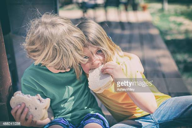 Two children eat lunch on a porch step outside