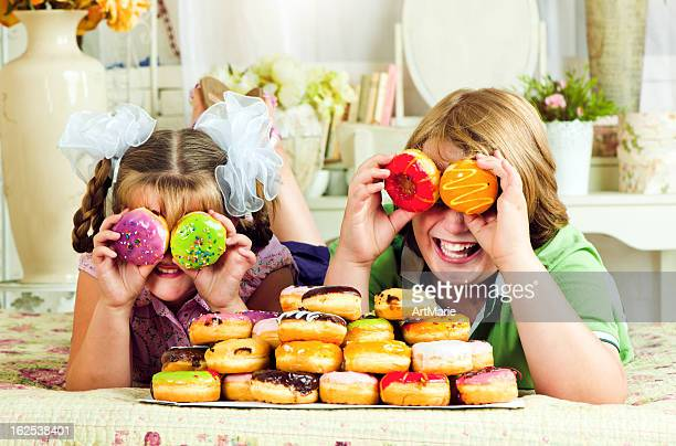 Two children eating donuts