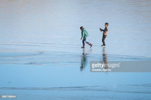 Two children enjoy the cold weather on frozen surface of Lake Van on December 12 2017 in Van Turkey
