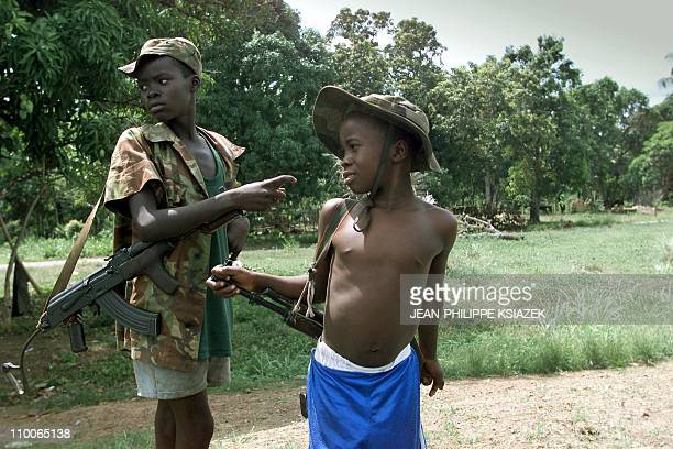 Two children enrolled with Sierra Leonean troops fighting rebels of the Revolutionary United Front get ready to fight on the frontline 16 May 2000...