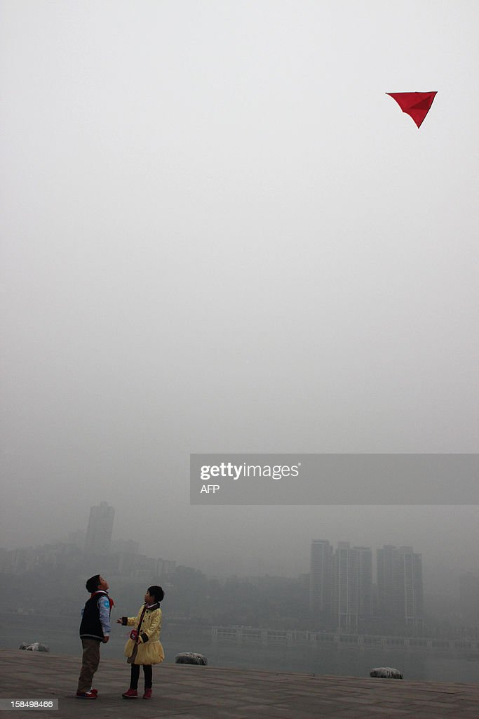 Two children fly a kite by a river next before buildings in Chongq-ing under dense fog on December 18, 2012. The cost of new homes increased in more Chinese cities in November than in the previous month, official figures showed on December 18, despite efforts from the government to keep the market in check. CHINA