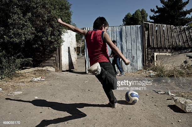 Two children from a low income neighbourhood play football in a street while they wait for Brazilian football legend Edson Arantes do Nascimento...
