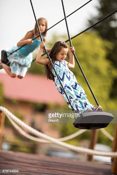 Two children having fun on swings at the playground.