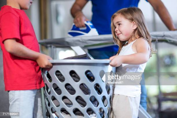 Two children helping father with chores carrying laundry basket