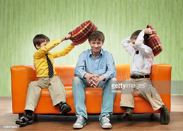 Two children hitting their father with pillows on a sofa