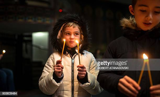 Two children hold candles during a religious mass to celebrate the Orthodox Christmas at the Cathedral of St Clement in Skopje on January 7 according...