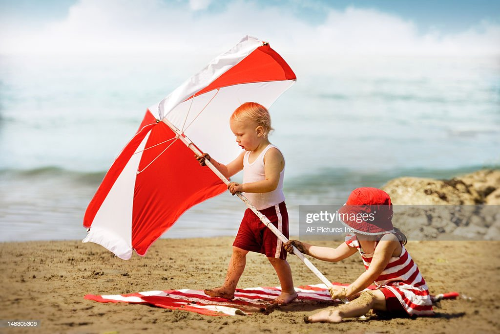 Two children holding a red umbrella on the beach : Stock Photo