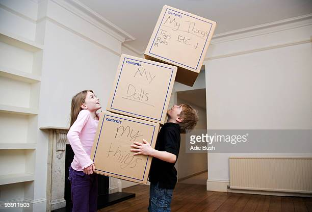 Two children holding a stack of boxes