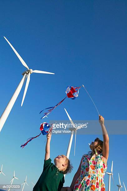 Two Children Holding Pinwheels and Standing in a Wind Farm