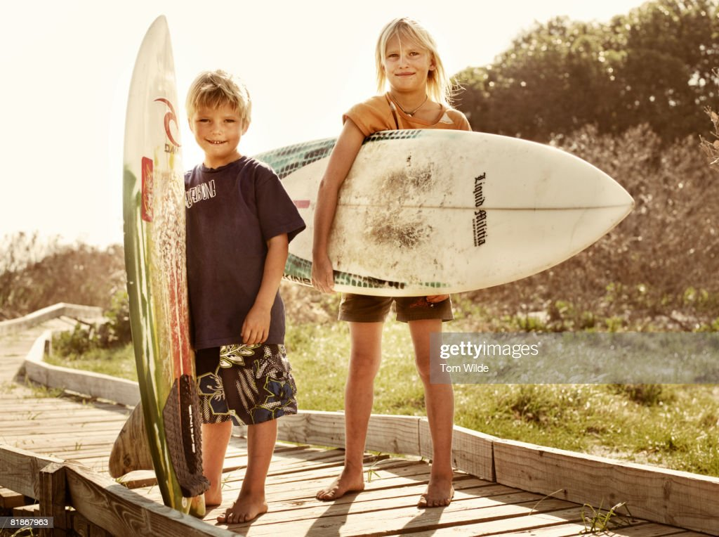Two children holding surf boards : Stock Photo
