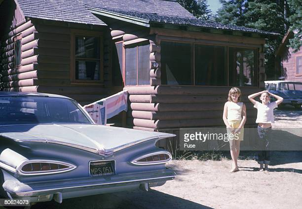 Two children in front of a cabin