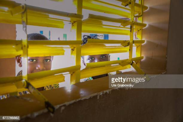 Two children in preschool age look through blinds in a classroom at a school of the Dreyer Foundation Here children are cared for and will be...