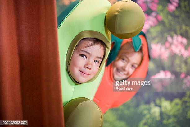Two children (5-9) in school play, looking out from behind curtain