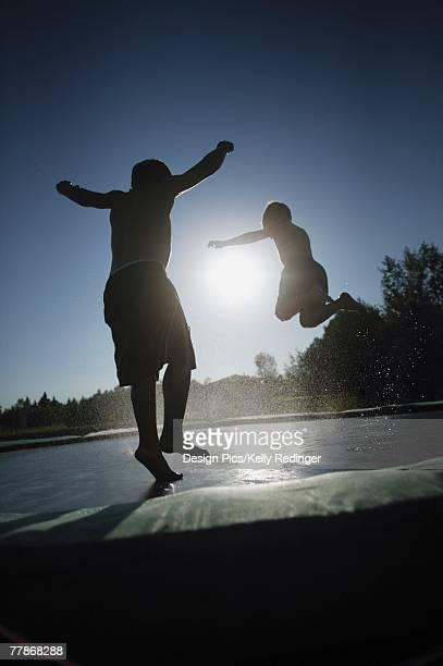 Two children jumping on a trampoline