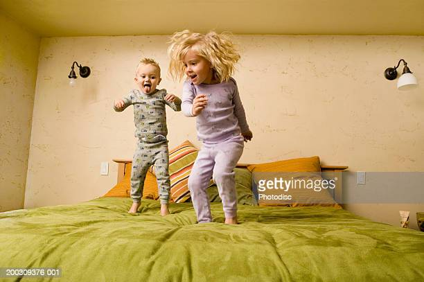 Two children (3-4), (4-5), jumping on bed