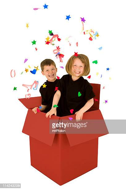 Two children jumping out of a Christmas present