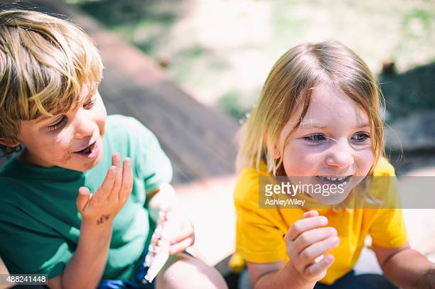 Two children laugh eating lunch