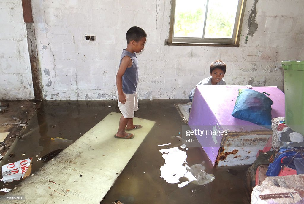 Two children look at the flooding in a house at Majuro Atoll in the Marshall Islands on March 3 after a king tide coupled with storm surges causing...