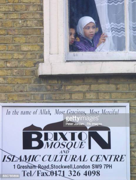 Two children look out of a window in the Brixton Mosque and Islamic Cultural Centre in London where a man who was arrested after being found with...