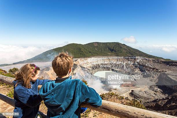 Two children looking in the crater of Poas volcano
