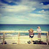 Two children looking out at ocean