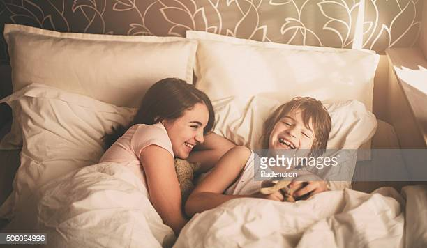 Two children lying in bed and playing