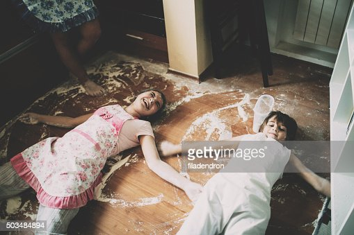 Two children lying on floor in kitchen