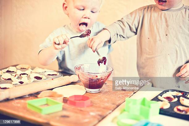 Two children making homemade jam tarts