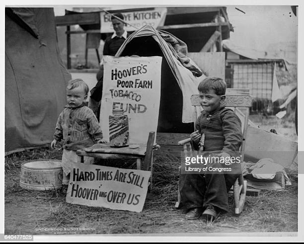 Two children of an unemployed veteran in the 'Bonus Army' camped out in Washington DC sit next to two signs One sign by a donation jar designates it...