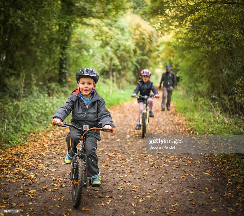 Two children on bicycles with father
