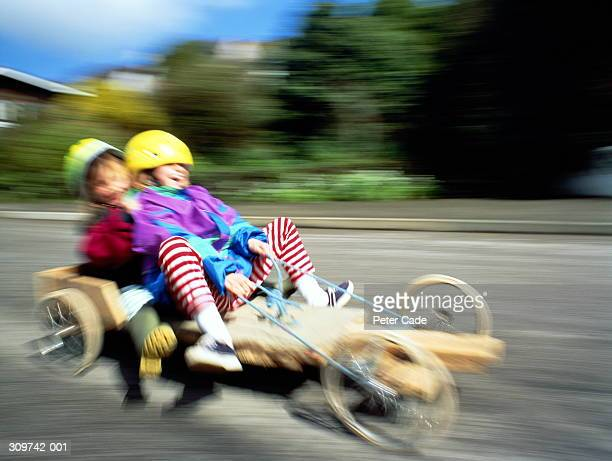 Two children (5-8) on home-made go-kart (blurred motion)