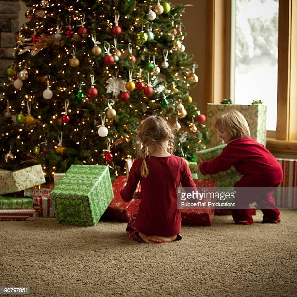 two children opening gifts on christmas morning