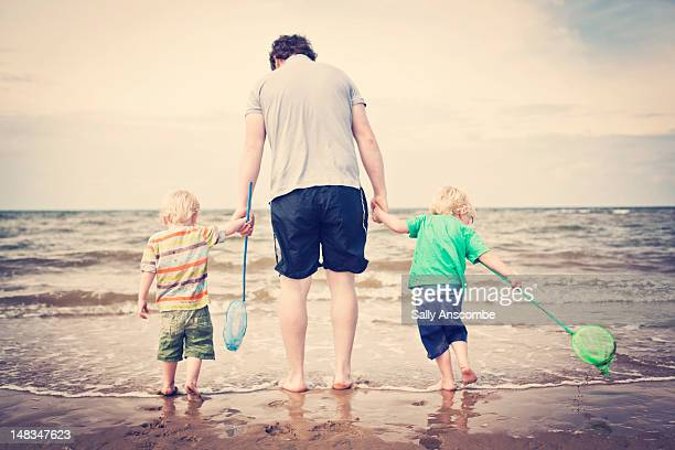 Two children paddling in sea with daddy