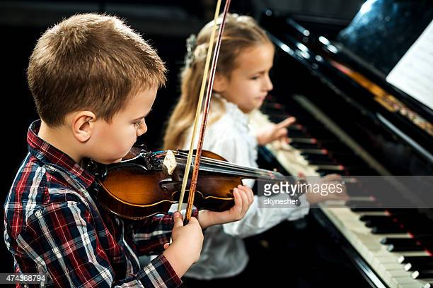 Two children performing classical music concert.