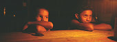 Two children pictured at their home a traditional reed hut in a small settlement in a protected reserve in the rainforest The Floresta Nacional do...