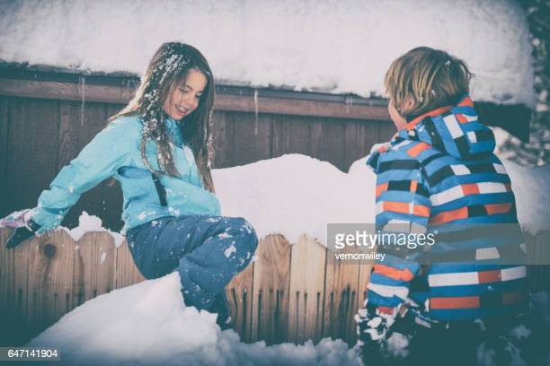 Two children play by a fence in snow