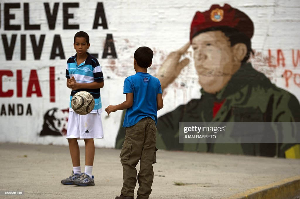 Two children play football near a mural of Venezuelan President Hugo Chavez in Caracas on December 31, 2012. Vice President Nicolas Maduro reported on national radio and television from Havana that President Chavez suffered further complications from respiratory infection that arose after undergoing surgery on December 11. AFP PHOTO/JUAN BARRETO