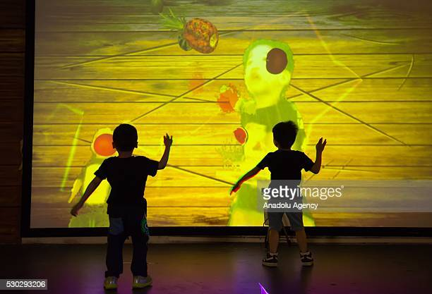 Two children play fruit ninja game in front of a screen at the MAG Universal magic world in Guangzhou China on May 102016 MAG Universal magic world...