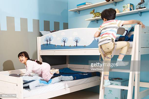 Two children play in a bunk bed.