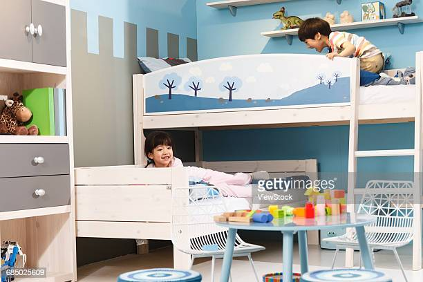 Two children play in a bunk bed