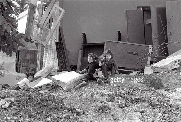 Two children play in their destroyed home in the village of Burj Rahal 24 February 1985 after Israeli forces besieged the villages of Deir Qanun...