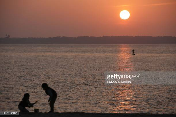 Two children play on the beach as a man paddles on Arcachon Bay near Cap Ferret at sunset on April 10 2017 off the coast of Arcachon / AFP PHOTO /...