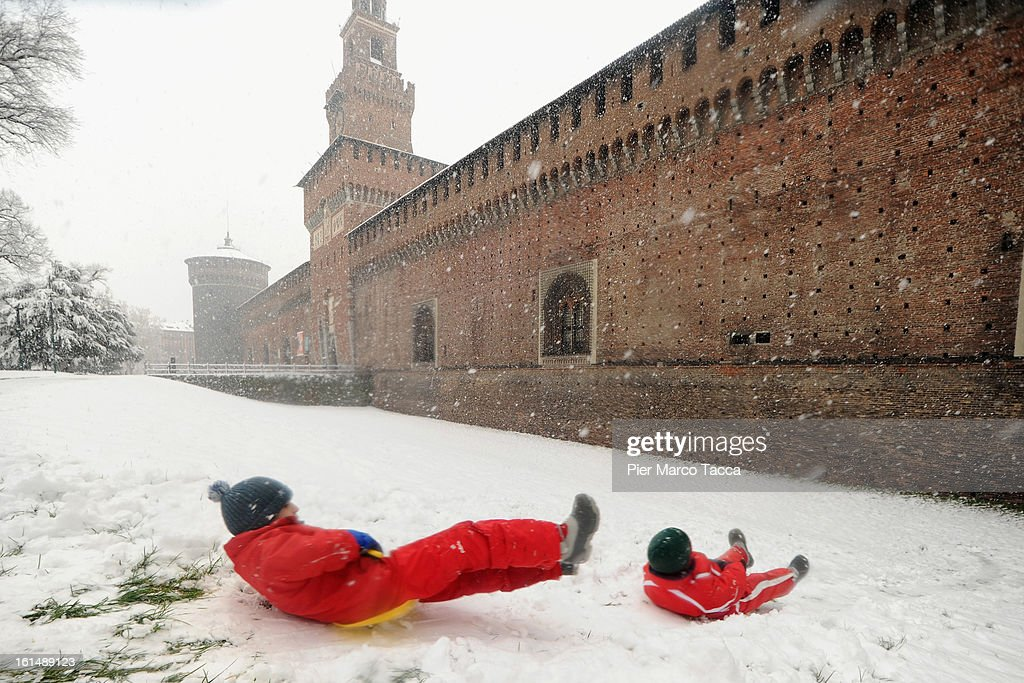 Two children play under the snow next to the Sforzesco castle on February 11, 2013 in Milan, Italy.Wind, snow and tempetarture under zero over the country has affected regions from North Italy to South Italy, transports has been affected with train cancellations and road closures.
