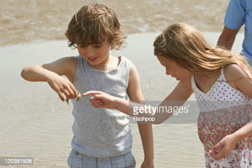 Two children playing at the beach : Stock Photo