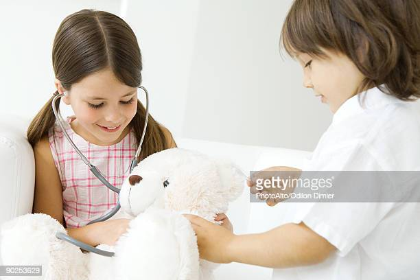 Two children playing doctor, girl listening to teddy bear's heart with stethoscope
