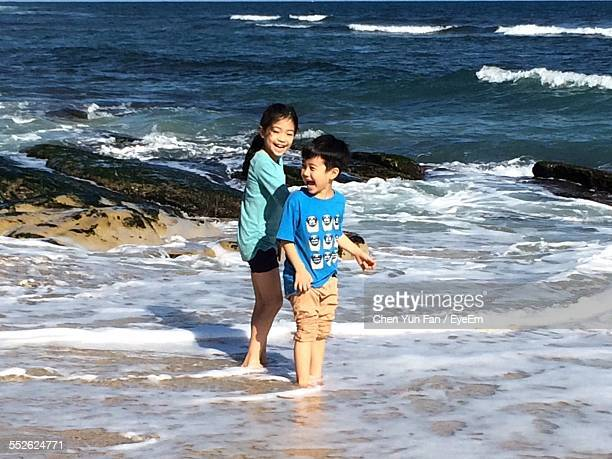 Two Children Playing In Sea