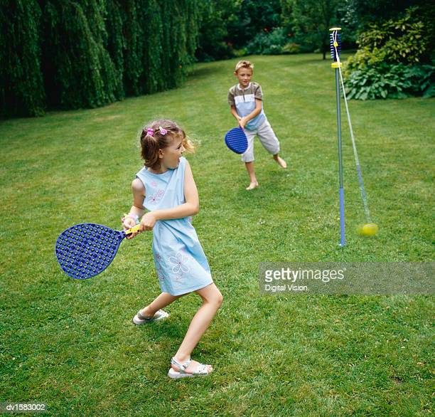 Two Children Playing Paddle Ball