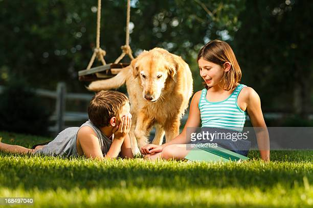 Two children playing with dog in the garden